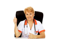 Smile elderly female doctor or nurse sitting behind the desk and shows thumb up Stock Photography