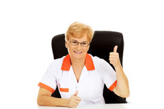 Smile elderly female doctor or nurse sitting behind the desk and shows thumb up Royalty Free Stock Photography