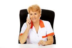 Smile elderly female doctor or nurse sitting behind the desk and talking through a phone Royalty Free Stock Photos