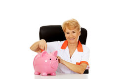 Smile elderly female doctor or nurse sitting behind the desk wit piggybank Stock Photos