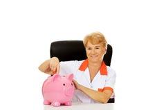 Smile elderly female doctor or nurse sitting behind the desk wit piggybank Royalty Free Stock Photos