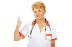 Smile elderly female doctor with stethoscope shows thumb up Royalty Free Stock Image