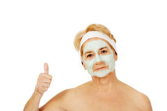 Smile elderly woman with facial mask shows thumb up Stock Photo