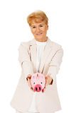 Smile elderly woman holding piggy bank Stock Images