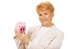 Smile elderly woman holding piggy bank Royalty Free Stock Photo