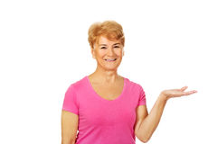 Smile elderly woman presenting something on open palm.  royalty free stock photography