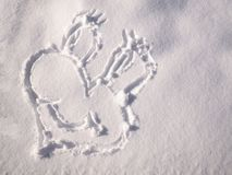Smile emoji painted on the snow, close-up, top view royalty free stock photography