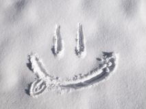 Smile emoji painted on the snow, close-up, top view stock photos