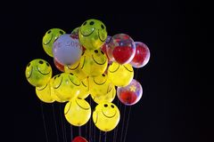 Smile emoji shaped yellow balloon and heart shaped red balloons tied in bunch with threads in black background.  stock photography