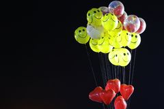 Smile emoji shaped yellow balloon and heart shaped red balloons tied in bunch with threads in black background.  royalty free stock photos