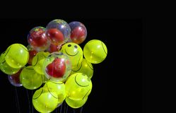 Smile emoji shaped yellow balloon and heart shaped red balloons tied in bunch with threads in black background. String gas anniversary up congratulation white royalty free stock image