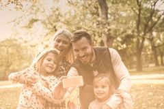 Smile everyone!. Smiling father taking self picture of family in nature stock image