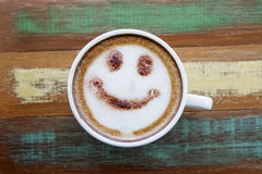 Smile face drawing on latte art coffee. Wood color background royalty free stock images