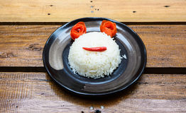 Smile face by rice and vegetable. On black dish at wood table royalty free stock image