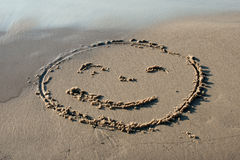 Smile face written in the sand Royalty Free Stock Image