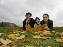 Smile faces of family on autumn leaves. Parents with child lie royalty free stock image