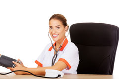 Smile female doctor or nurse checking blood pressure patient Royalty Free Stock Photo