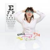 Smile female face chooses spectacles on eyesight test chart. Background, eye examination ophthalmology concept Stock Photo