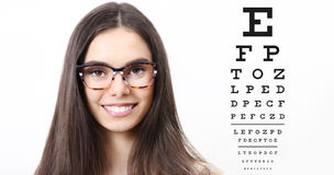 Smile female face with spectacles on eyesight test chart backgro. Und, eye examination ophthalmology concept Royalty Free Stock Images