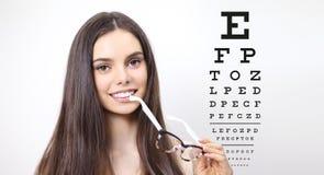 Smile female face with spectacles on eyesight test chart. Background, eye examination ophthalmology concept Stock Image