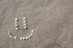 Smile figure laid out on the sand from the shells. royalty free stock images
