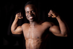 Smile flex muscles. A man flexing his muscles on a black background Stock Photography