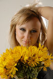 Smile and flowers. There is women with yellow flowers looks at you stock photos
