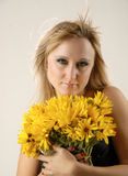 Smile and flowers. There is women with yellow flowers looks at you royalty free stock photography