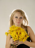 Smile and flowers. There is women with yellow flowers looks at you royalty free stock photos