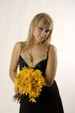 Smile and flowers. There is women with yellow flowers looks at you stock photo