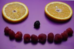 Smile from fresh berries and fruit on the purple background stock images