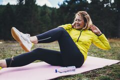 Free Smile Girl Exercising Outdoors In Green Park, Activity Pose With Stretch Legs, Happy Woman Laughing Stretching Exercises Training Stock Photo - 180966090