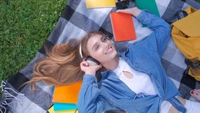Smile girl student listening music outdoor, lying on grass and relaxing. Teenage female listening music outdoor, lying on grass and relaxing stock video footage