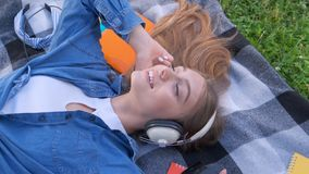 Smile girl student listening music outdoor, lying on grass and relaxing. Teenage female listening music outdoor, lying on grass and relaxing stock footage