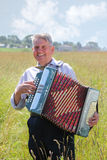 Smile grandfather plays on accordion Royalty Free Stock Photo