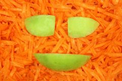 Smile green apple on the carrot background Stock Photo