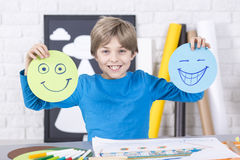 Smile or grin?. Happy young boy holding pieces of papers with smile and grin. On the desk colorful pens and a picture Royalty Free Stock Images
