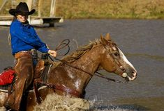 Smile and Hang On. Cowgirl smiles while hanging on to reins of her horse splashing through pond stock image