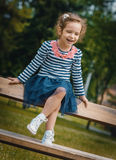 Smile happy little girl sitting on the bench Royalty Free Stock Images