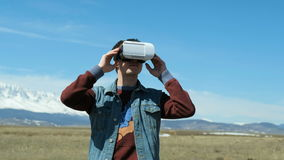 Smile happy man getting experience using VR-headset glasses of virtual reality with sky and cloud background 20s 4k. Smile happy man getting experience using VR stock video