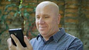 Smile Happy Reading för entusiastisk affärsman bra finansiell nyheterna på mobiltelefonen royaltyfri bild
