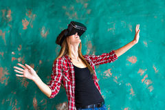 Smile happy woman getting experience using VR-headset glasses of virtual reality much gesticulating hands Stock Photo