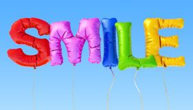 Smile inscription from multicolored balloons on the blue sky, 3D Stock Photo