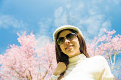 Smile lady with pink cherry flower and blue sky Royalty Free Stock Photo