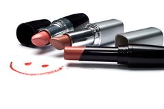 Smile and lipsticks. Three lipsticks and smile on a white background Stock Images