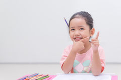 Smile little asian girl with pencil color on white background Royalty Free Stock Image