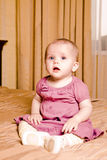 Smile little baby in red dress sitting on the floor Stock Images