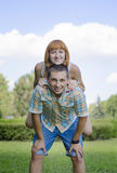 Smile of lovers and cheerful people. The girl sits on shoulders of the guy, against the blue sky and green a lawn Stock Photography