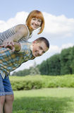 Smile of lovers and cheerful people. The girl sits on shoulders of the guy, against the blue sky and green a lawn Royalty Free Stock Images