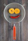 Smile made with peeled mandarine tangerine as eyes, pepper chili  mouth in metal sieve colander. Smile made with peeled mandarine tangerine as eyes, pepper chili Stock Photo